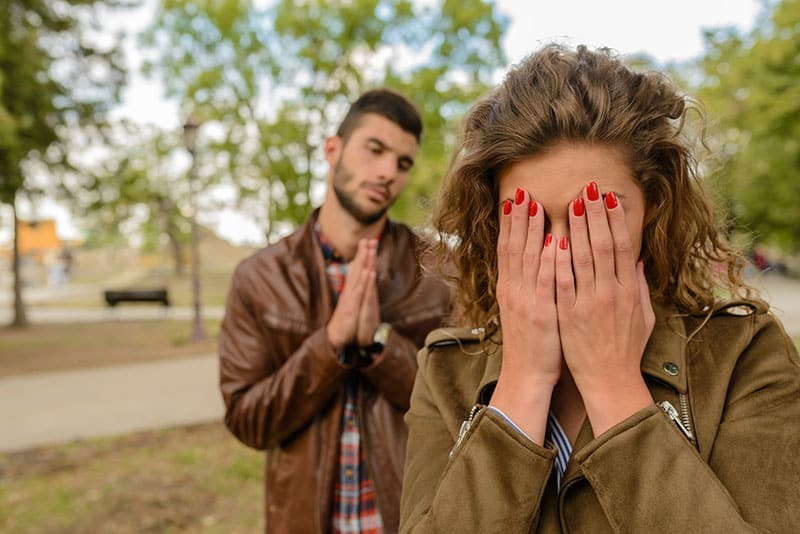 Crying Woman With Green Jacket Behind Man With Brown Leather Jacket asking forgiveness at Daytime