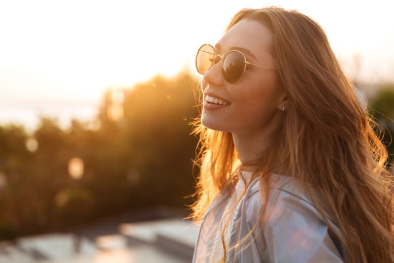 happy young woman smiling at sunset