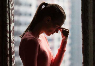 worried woman standing by window