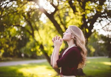 blond woman praying in the nature