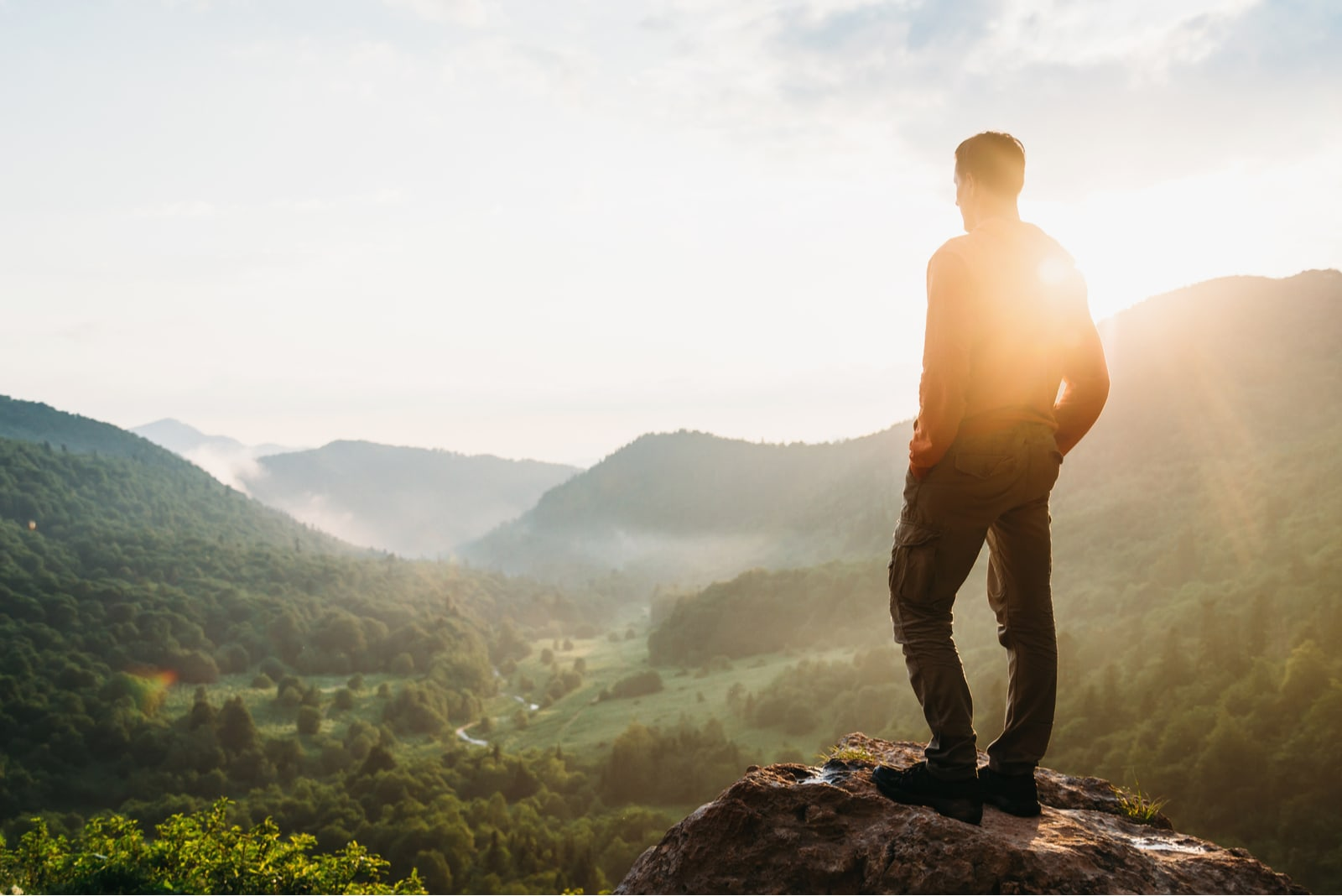 Traveler young man standing in the summer mountains