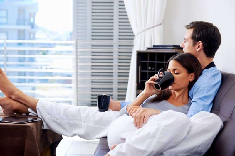 chill couple lying on couch in living room and drinking tea
