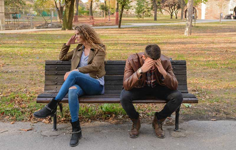 Couple Woman and Man quarrel while sitting on bench