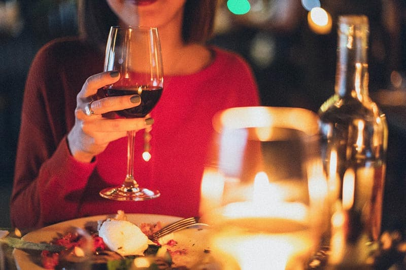 Woman holding wine glass dinner date