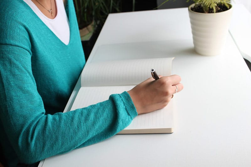 Woman writing on notebook white desk