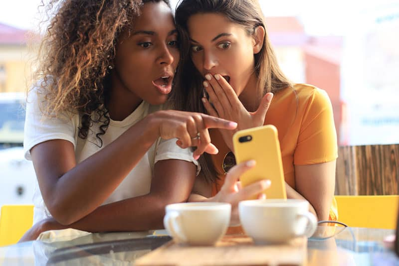 Two girlfriends wondering something on the phone