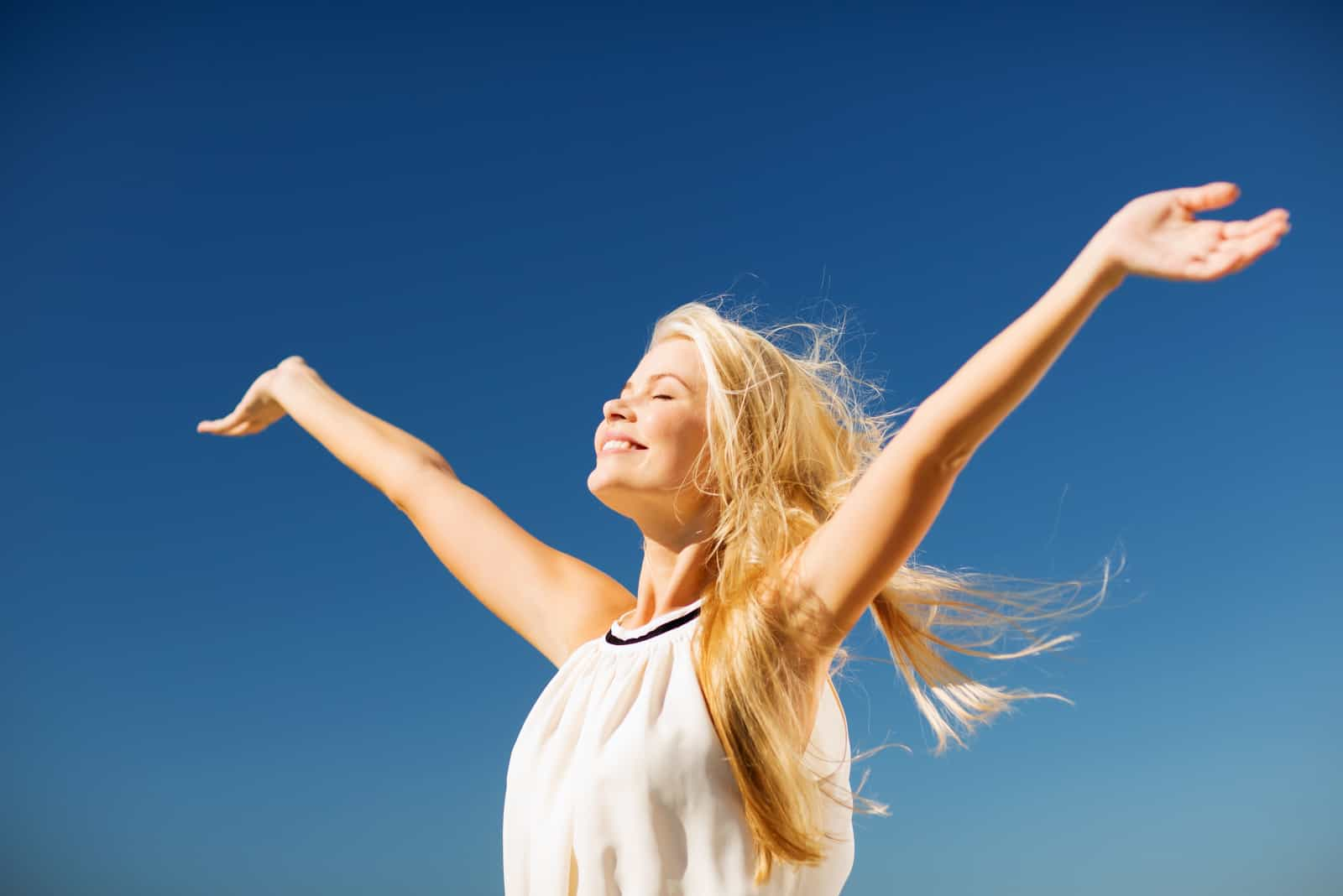 a beautiful woman with long blonde hair stands with her arms outstretched