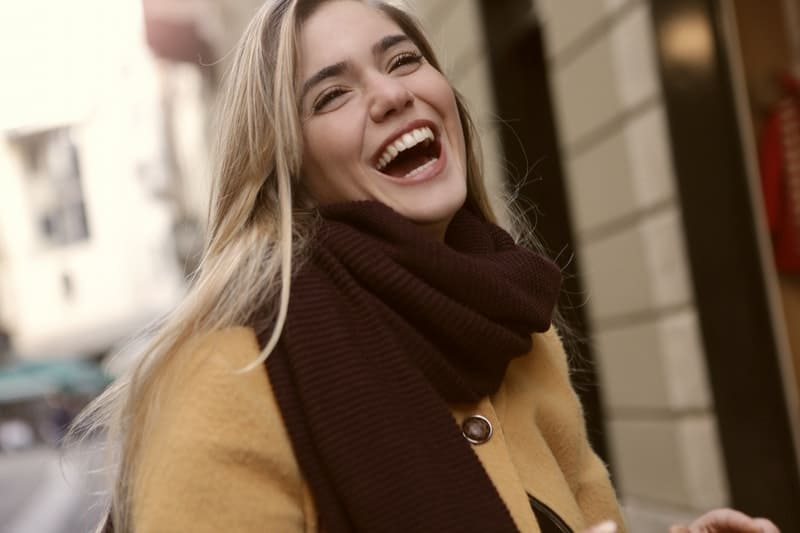 a blonde joyous woman in coat