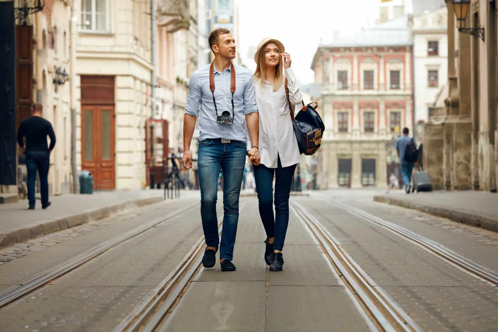 a man and a woman walk down the street holding hands