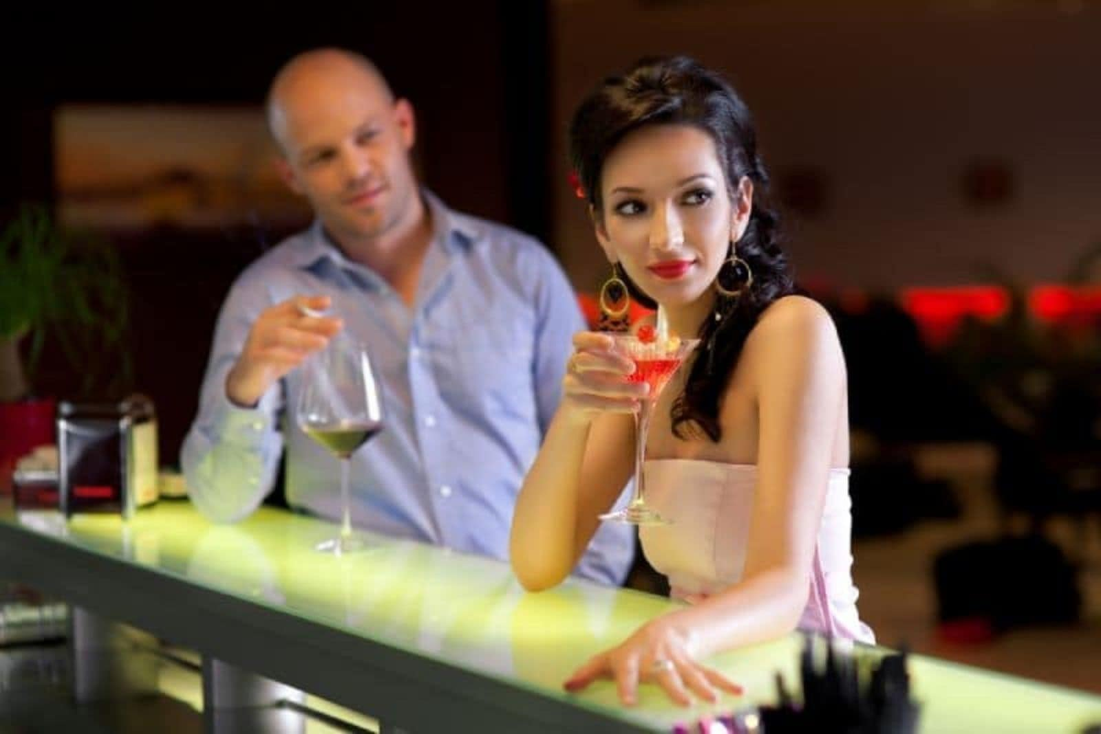 a man drinks wine and looks at a woman