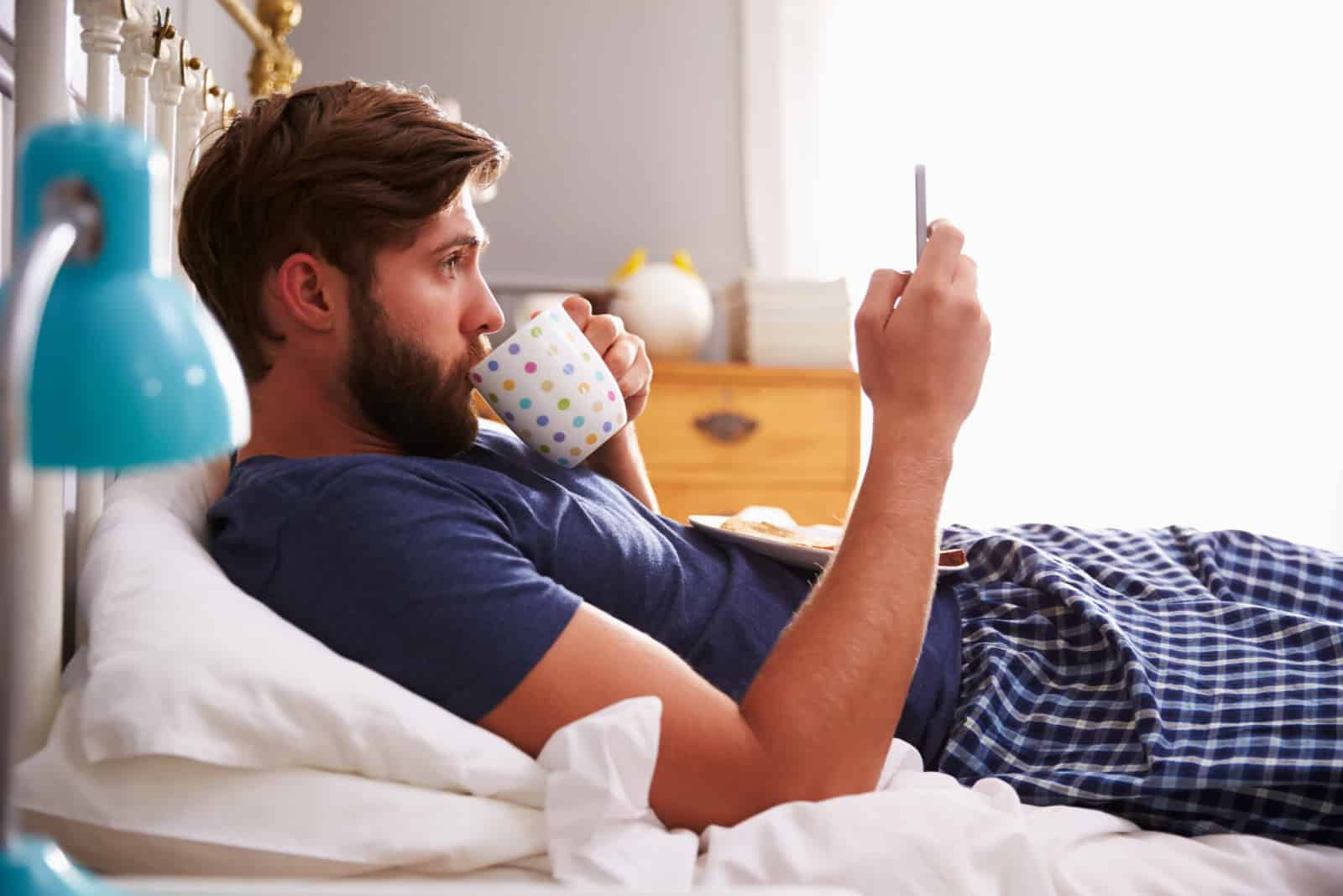 a man lies on the bed drinking coffee and pressing a phone