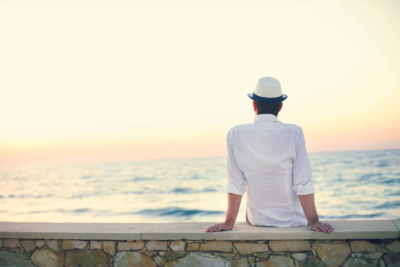a man with a white hat on his head sits on the wall and looks out to sea