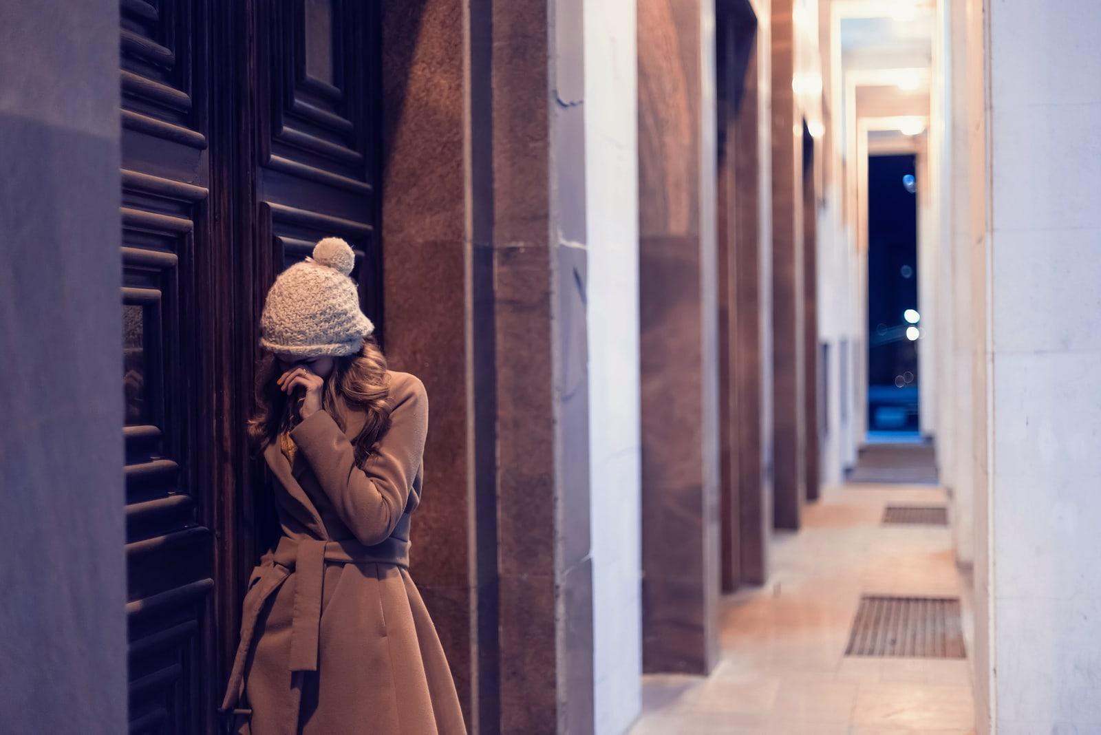 a sad girl in a brown coat stands in the hallway in front of the door