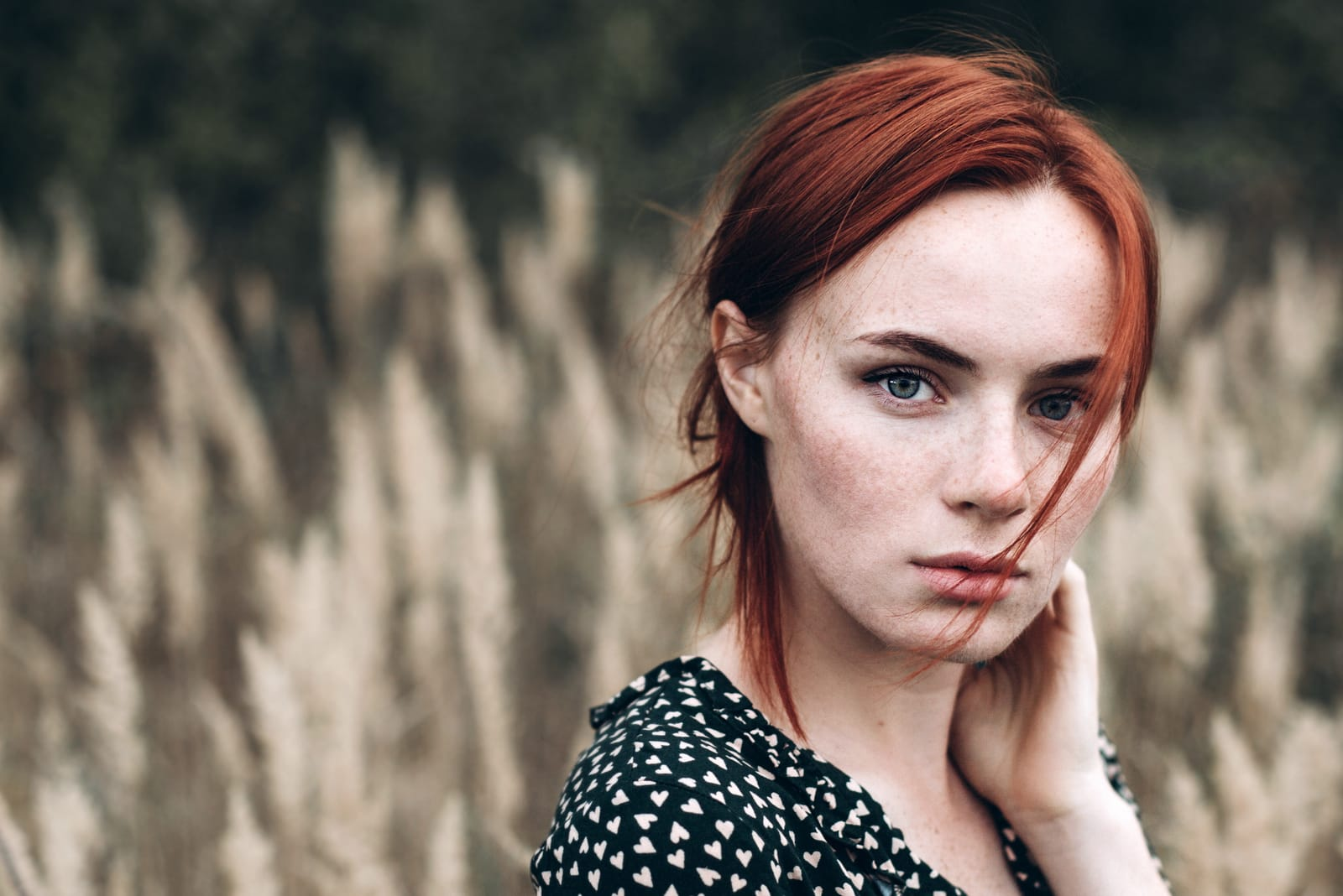 a sad red-haired girl stands in a field of wheat