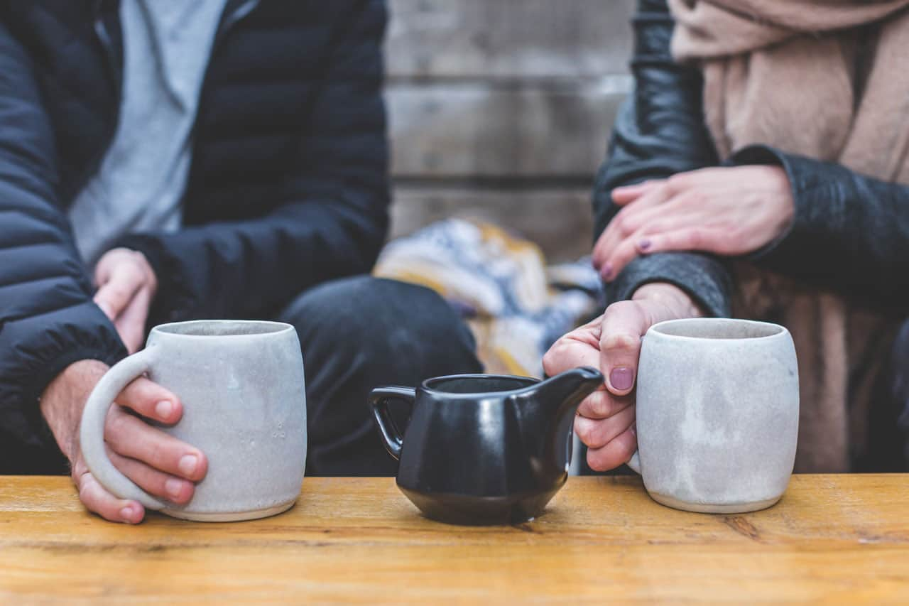 a tea conversation with hands on cups
