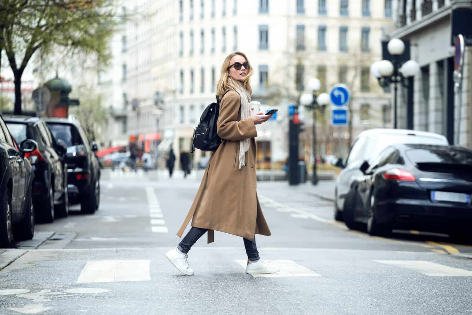 a woman in a brown coat walks down the street