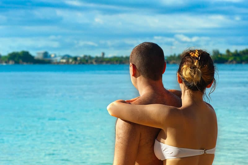 back view of an affectionate couple in swimwear facing the sea