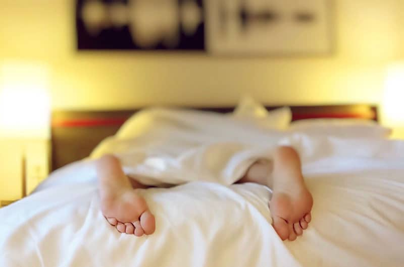 alone sleeping in bed showing 2 feet out of the linen