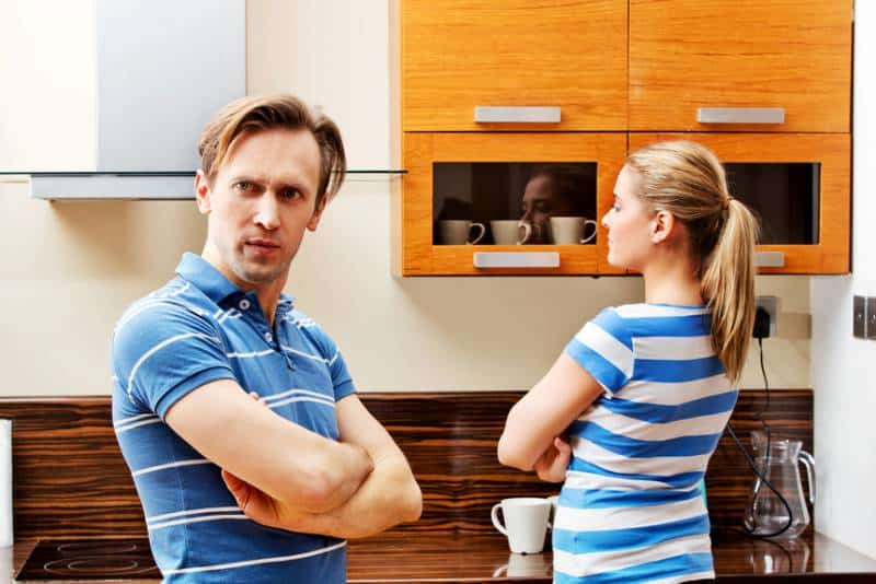 angry couple at kitchen with crossed arms