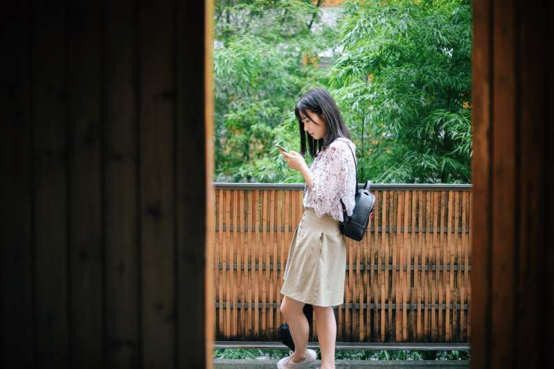 Asian young girl texting a message on her phone while walking in nature