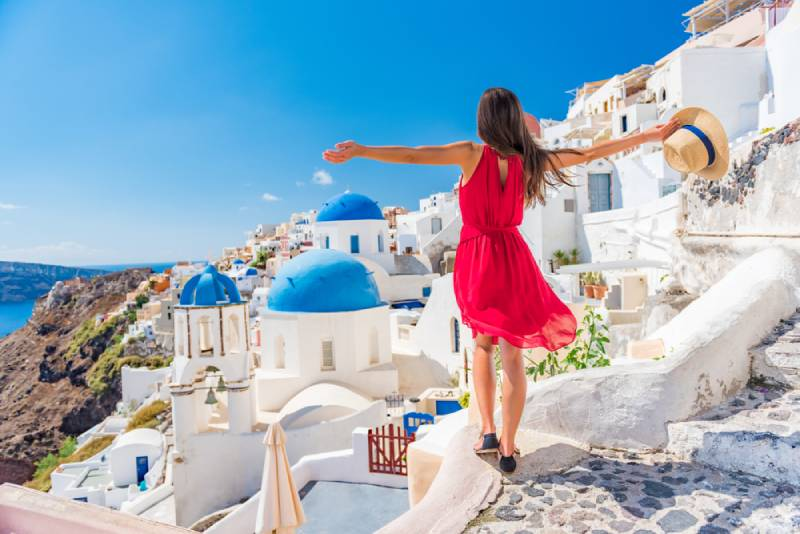 back view of traveling woman wearing red dress and standing with arms up in Santorini