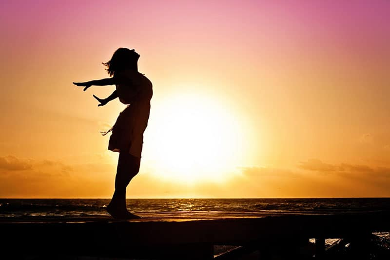 silhouette on the beach and woman and sunrise
