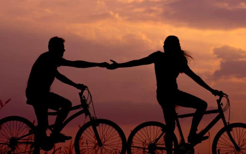Bicycle couple silhouettes holding hands in sunset