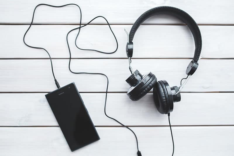 black headphones and cellphone in white plank table
