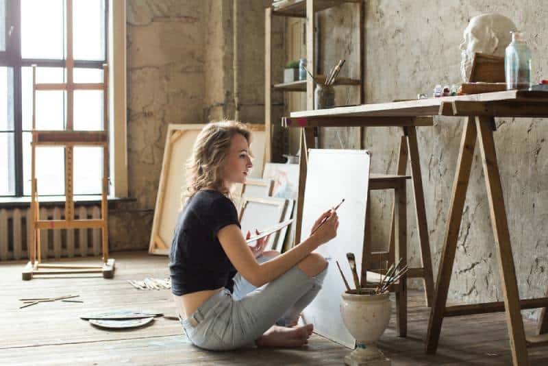 blonde girl sitting and painting on table