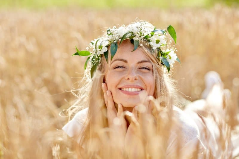 blonde smiling woman lying on cereal field