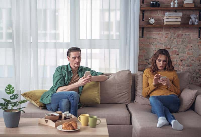 bored couple sitting in living room and looking at their smartphones