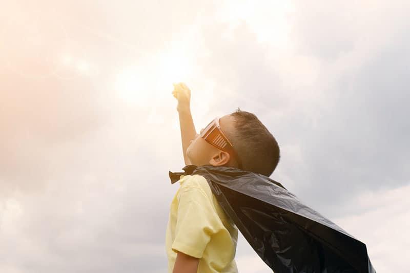 boy playing superhero using black plastic bag as cape