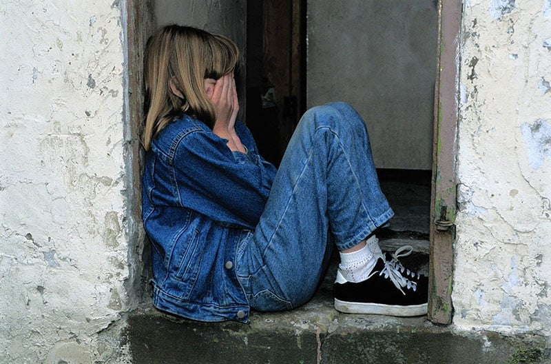 child crying in the doorway wearing denim covering her face