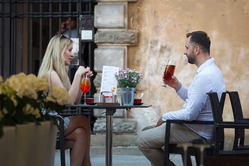 woman and man sitting at cafe table and drinking