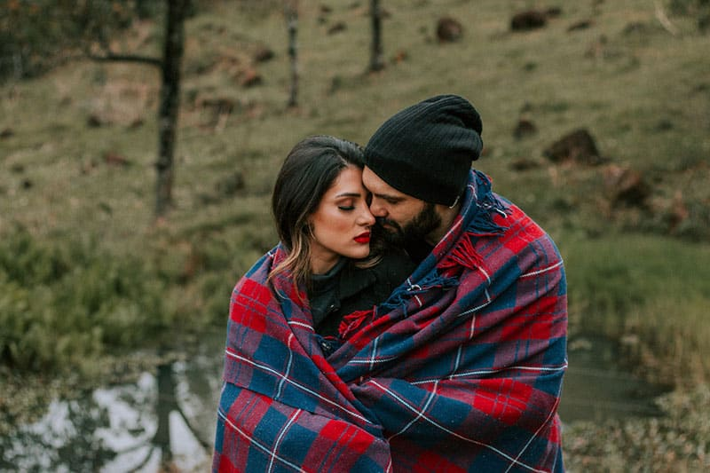 couple covered with blanket standing near a lake inside the woods