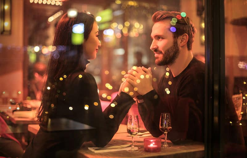 dating couple holding hands with lights reflecting on glass