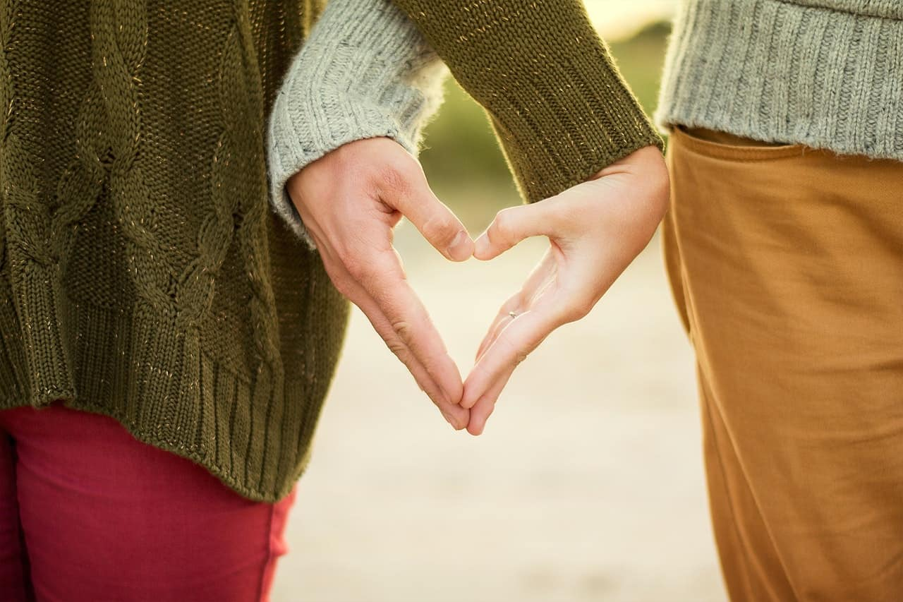 couple holding hands like sign of heart