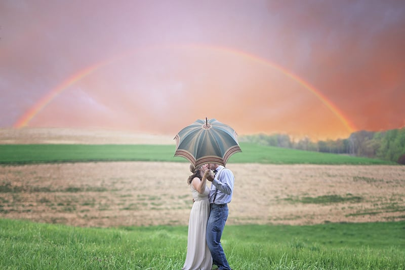 couple holding umbrella while kissing under the rainbow
