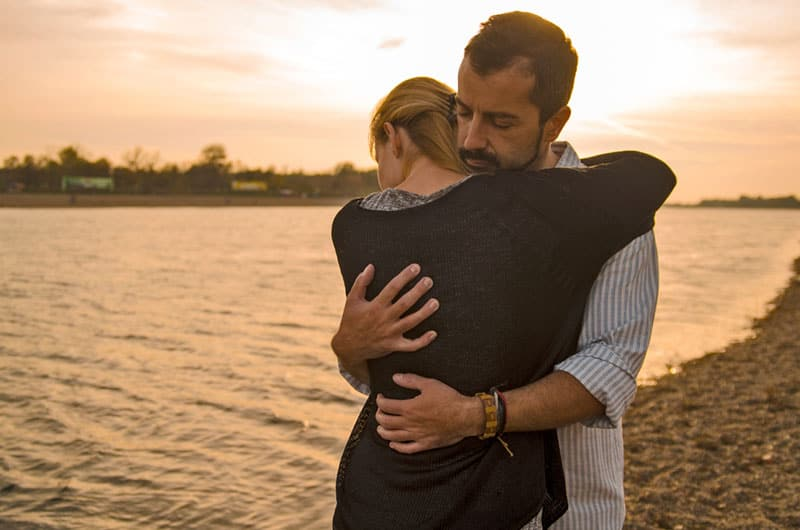 couple hugging by the lake