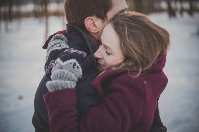 couple hugging tight on their winter suit