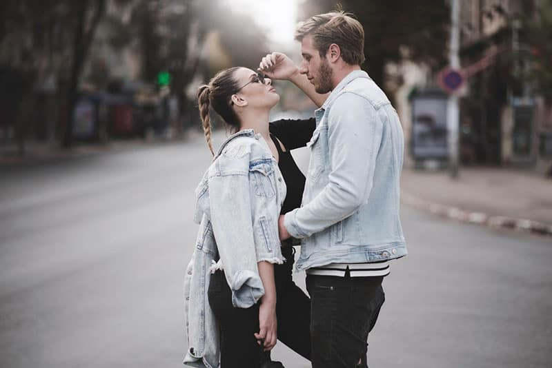 couple in denim facing each other in the middle of the street
