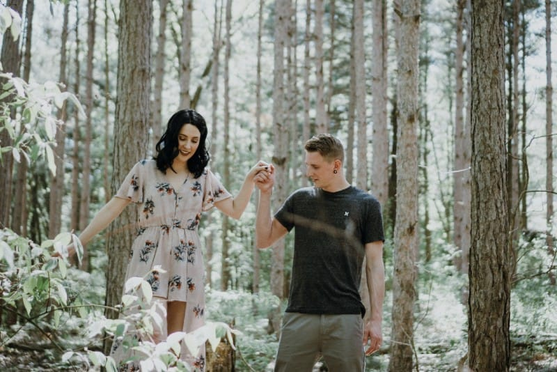 man holding woman's hand in forest