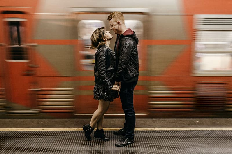 sweet couple in train station with moving train at the back