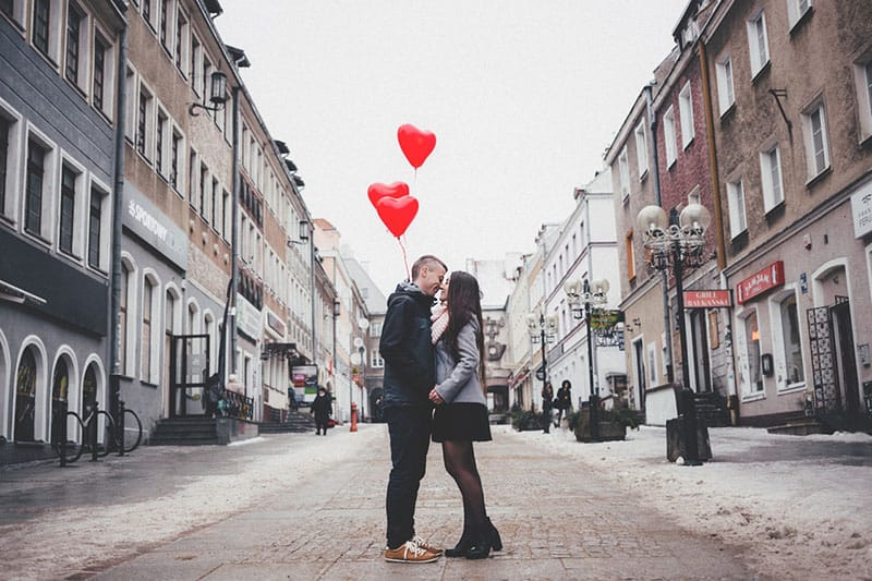 couple kissing in the street with red heart balloons
