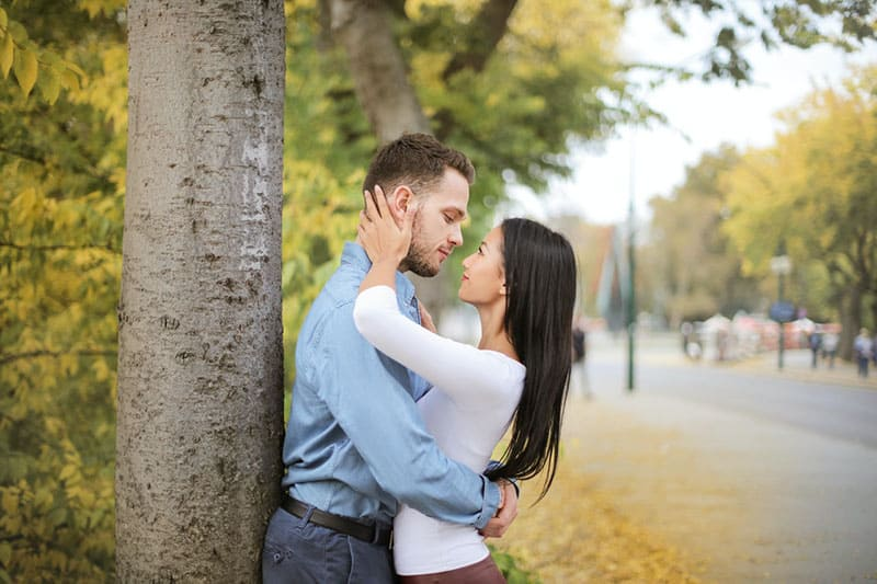 couple looking at each other leaning on a tree beside the streets