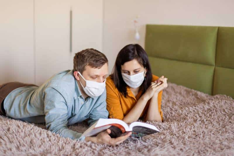 couple lying on bed with protective mask during self-quarantine