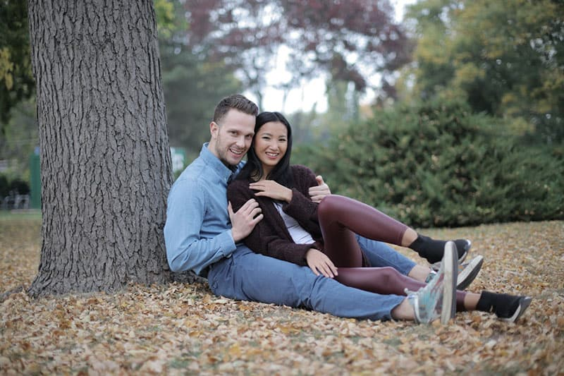 couple cuddling while sitting beside a tree