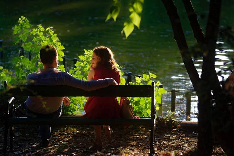 Couple sitting on bench in front of lake
