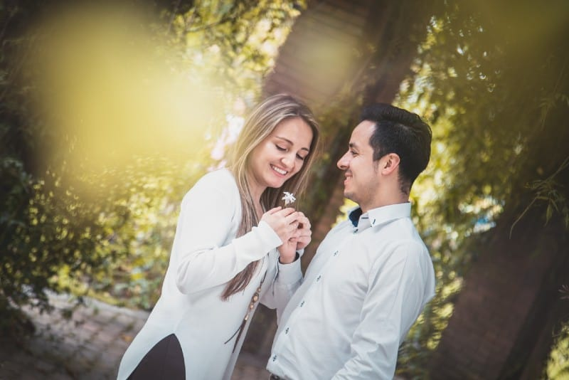 man giving white flower to woman surrounded by green trees