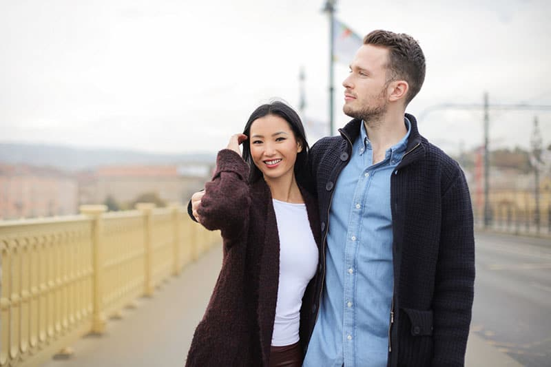 couple standing on sidewalk with man's arms around woman's shoulder
